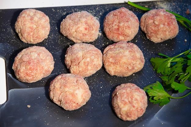 Cottura delle cotolette di carne. polpette semilavorate su tagliere.