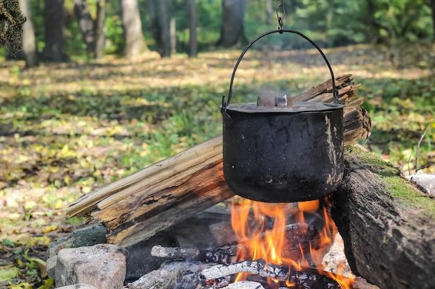 Cucinare nella natura. calderone in fiamme nella foresta