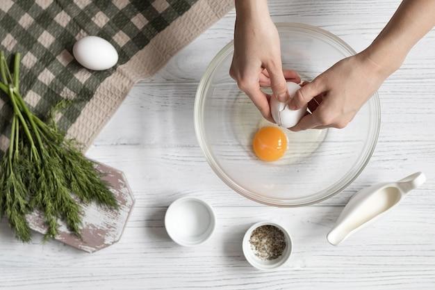 Cucina frittata con erbe aromatiche, mani femminili rompono un uovo, ricetta passo dopo passo, vista dall'alto