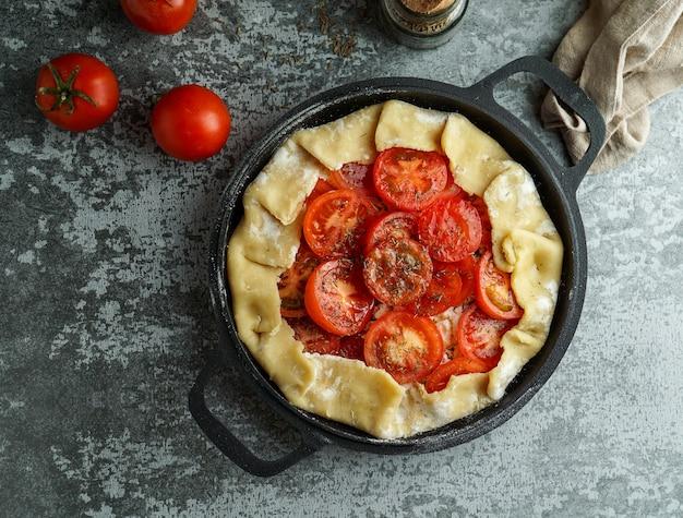 Cucina torta di pasticceria con feta chesse e pomodori, olio d'oliva e spezie