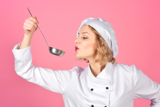 Ritratto di cucina di chef donna che tiene cucchiaio con cottura di cibi caldi e culinaria professionale