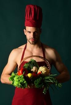Cucinare preparando per cena chef maschio con cesto di verdure