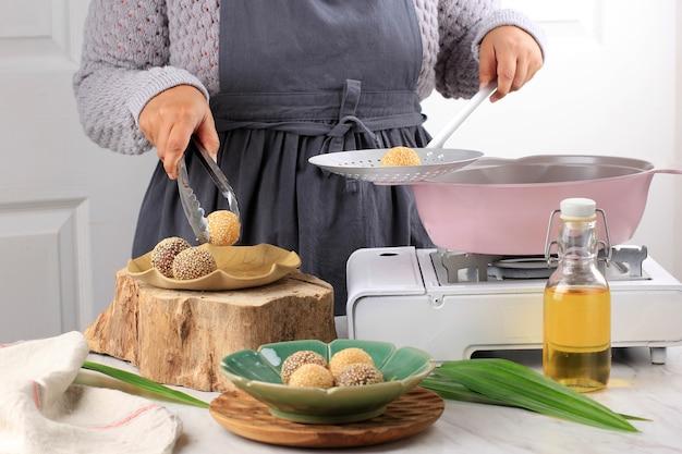 Processo di cottura: onde-onde di frittura a mano femminile asiatica, (palla di semi di sesamo) sulla piastra marrone con pinze in acciaio inossidabile, fritta fresca nell'olio caldo. processo di cottura in cucina fare onde