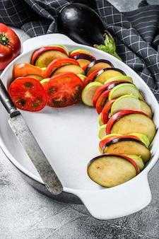 Cottura di ratatouille - tradizionale piatto di verdure provenzale francese. sfondo grigio. vista dall'alto.