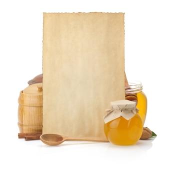 Ricette di cucina e vaso pieno di miele su bianco