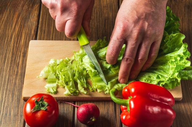 Insalata di cottura nella cucina del ristorante. lo chef è mani insalata tagliata in primo piano. insieme delle verdure per una dieta dell'insalata.