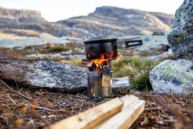 Cucinare su un piccolo fornello da campeggio in un campo di montagna.