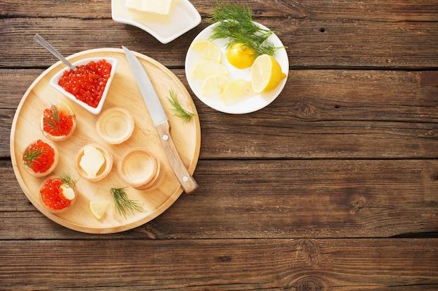 Tortine di cottura con caviale rosso sulla tavola di legno