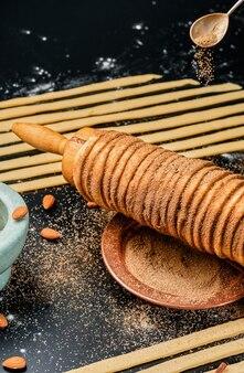 Cucina trdelnik. delicatezza al forno su spiedino e pasta di carbone con zucchero, cannella e vaniglia. dolci natalizi, street food. cucina ceca e morava.