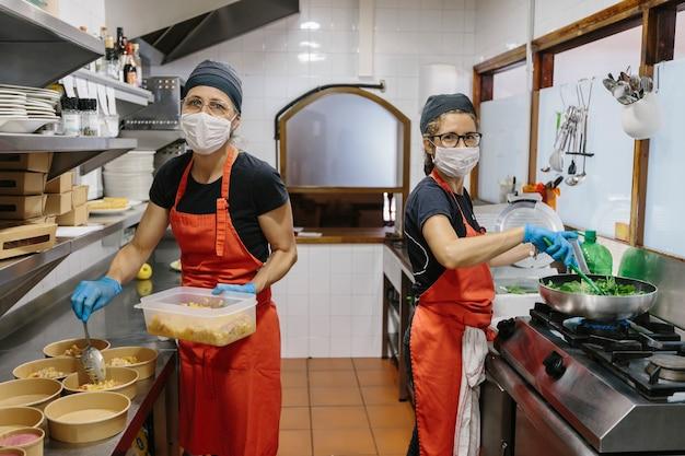 Cuochi in un ristorante protetto da una mascherina per precauzione contro il coronavirus preparando cibo da asporto. i contenitori utilizzati sono compostabili.