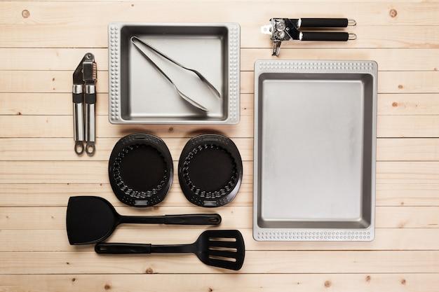 Pentole e accessori su un tavolo di legno. Foto Premium