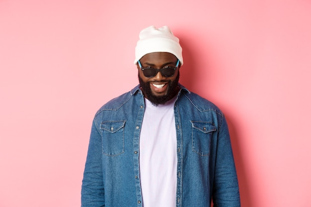 Cool hipster afroamericano uomo in berretto e occhiali da sole, sorridente soddisfatto e guardando la fotocamera, in piedi fiducioso su sfondo rosa.