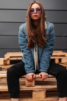 Fresca giovane donna hipster americana in abiti casual alla moda per giovani in eleganti occhiali viola posa all'aperto in città in primavera. il bellissimo modello urbano alla moda della ragazza si siede su pallet di legno all'aperto.