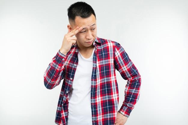 Ragazzo asiatico freddo in una camicia a quadri spalancata isolata