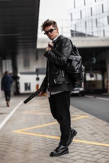Fresco giovane attraente in occhiali da sole in una giacca di pelle nera oversize di moda in jeans con stivali con un elegante zaino in piedi per strada in città. ragazzo europeo hipster in posa all'aperto.