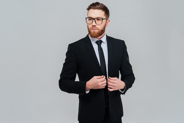 Uomo d'affari barbuto fresco con gli occhiali e vestito nero che guarda da parte. sfondo grigio isolato