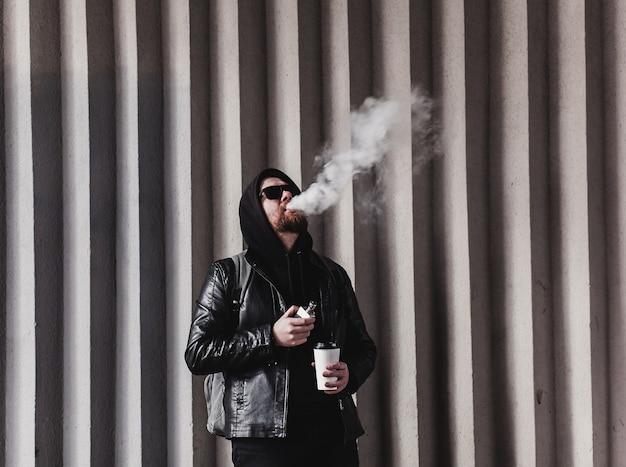 Un uomo barbuto alla moda fuma sigarette elettroniche e tiene in mano un caffè da asporto
