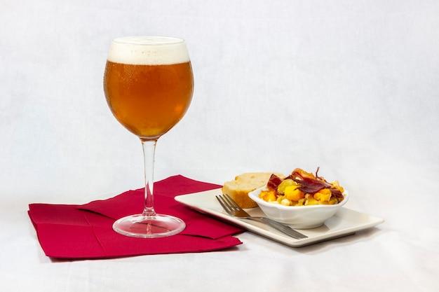Una birra fresca servita in un bicchiere di cristallo insieme ad un buon antipasto di uova con prosciutto e pane su sfondo bianco