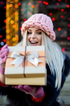 Bella modella bionda che indossa un berretto lavorato a maglia e un cappotto caldo, aprendo una confezione regalo sullo sfondo delle luci bokeh bokeh