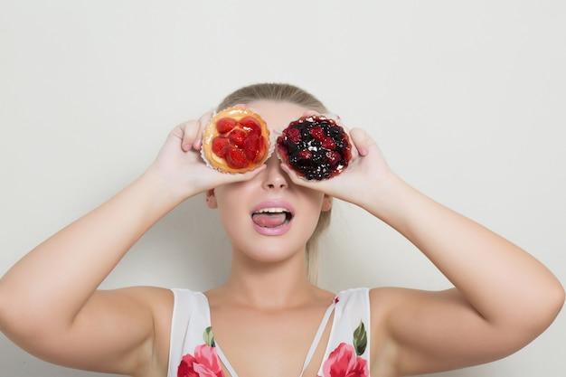 Bella donna bionda che tiene in mano un dolce con frutti di bosco e si copre gli occhi