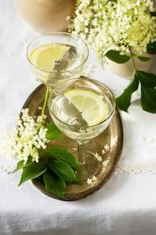 Una bevanda fresca con sciroppo di limone e fiori di sambuco in bicchieri su un vassoio di metallo. stile rustico.