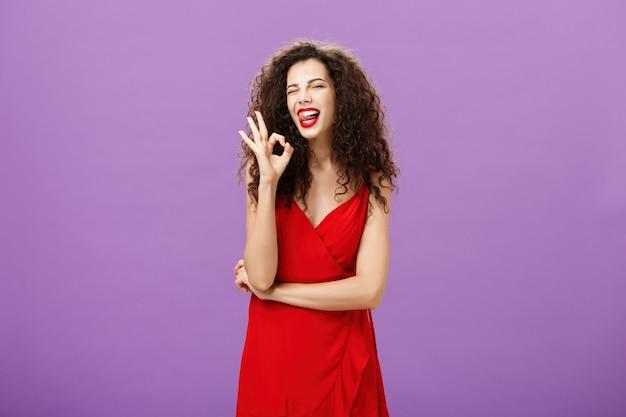 Bella donna caucasica entusiasta con l'acconciatura riccia che strizza l'occhio con gioia sporgendo la lingua e s...