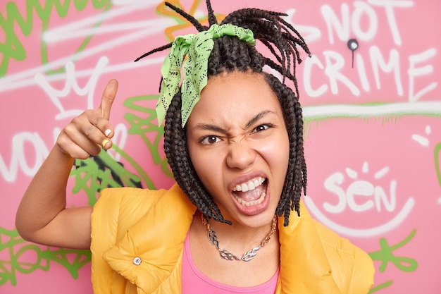 Fantastica ragazza hipster fantasia con i dreadlock pettinati fa il tuo gesto esclama e ha un aspetto sfacciato incontra gli amici che hanno interessi comuni disegna graffiti