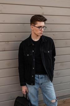 Moda giovane alla moda con gli occhiali con l'acconciatura in eleganti vestiti casual in denim con zaino in pelle nera vintage