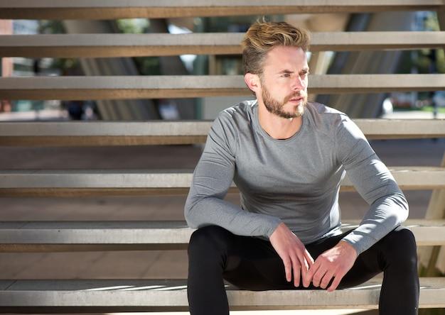 Cool uomo adatto che si siede sui gradini all'aperto