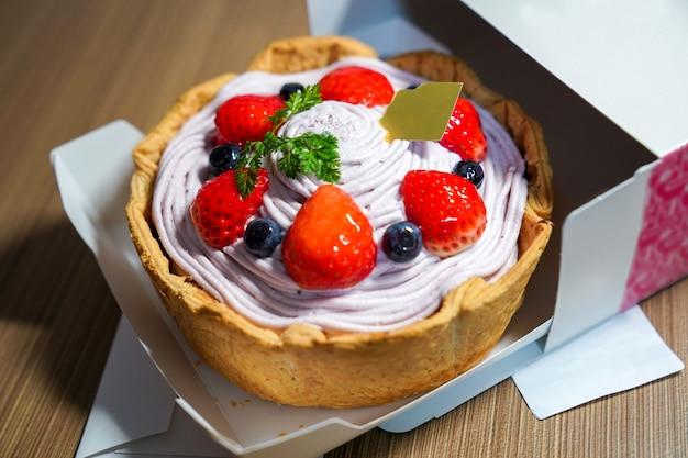 Crostata di formaggio fruttato fresco fresco; favore di crema di mirtilli guarnire con stawberry, mirtillo toglierlo dalla scatola di carta.
