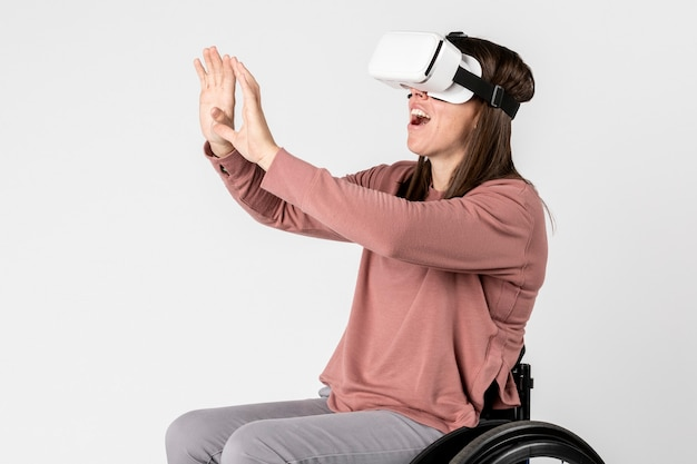 Bella ragazza su una sedia a rotelle che prova un visore vr