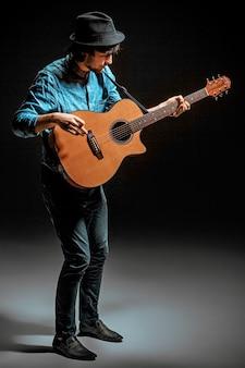 Ragazzo figo con cappello in piedi con la chitarra su sfondo scuro studio