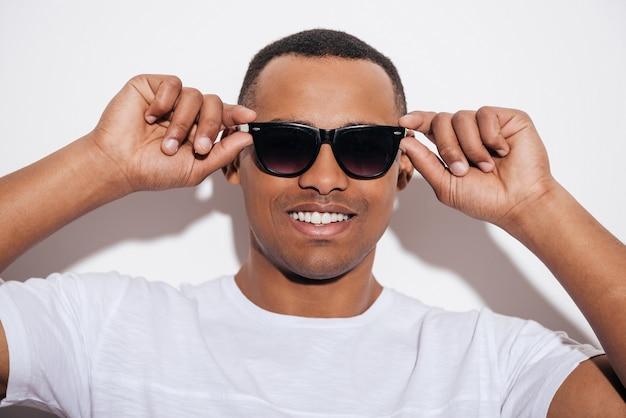 Fresco e bello. fiducioso giovane africano che si aggiusta gli occhiali da sole e sorride
