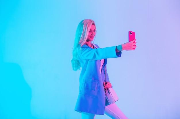 Bella giovane donna d'affari felice in abiti luminosi alla moda con blazer scatta foto selfie sul telefono in studio su sfondo chiaro rosa neon