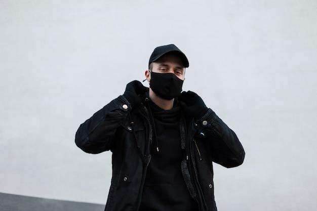 Uomo cool hipster con maschera protettiva medica e berretto nero in abiti neri alla moda con giacca ed elegante felpa con cappuccio vicino al muro bianco sulla strada. stile urbano moderno pandemico maschile