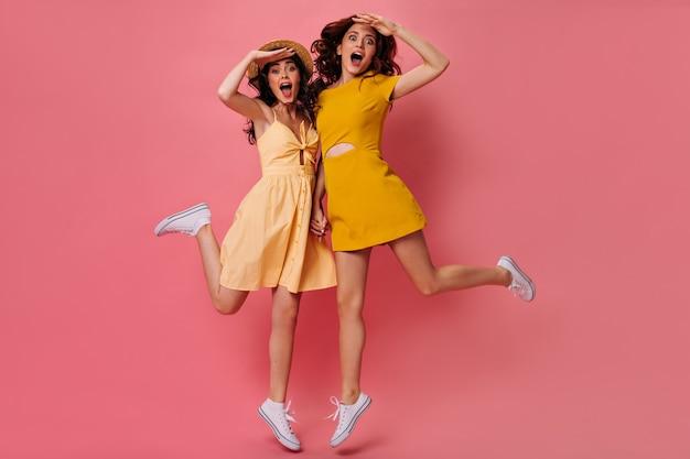 Belle signore in abiti gialli che saltano sul muro rosa