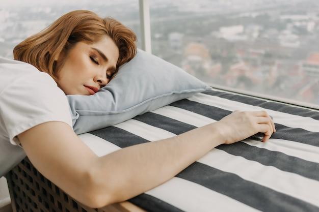 Una donna dall'aspetto fresco sta riposando e guarda la vista dal suo appartamento