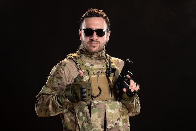 Fantastico soldato maschio in mimetica sul muro nero