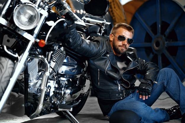 Motociclista freddo dell'uomo in occhiali da sole che si siedono vicino al suo motociclo