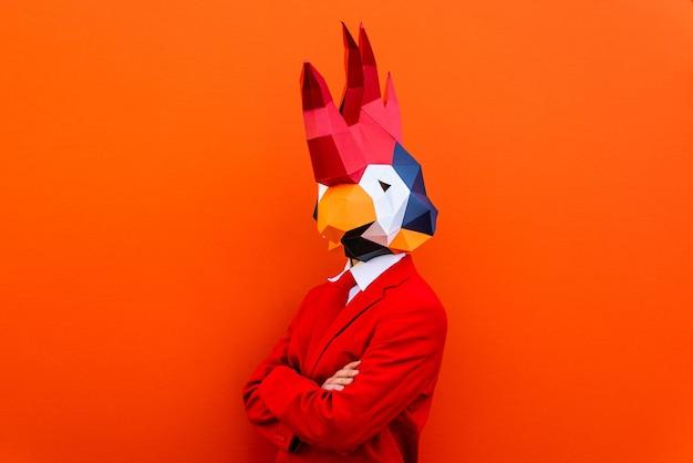 Uomo figo che indossa una maschera origami 3d con abiti colorati alla moda - concetto creativo per la pubblicità, maschera testa di animale che fa cose divertenti su sfondo colorato
