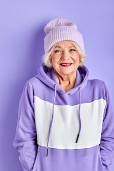 Cool moderna donna anziana in pullover viola e cappello in posa