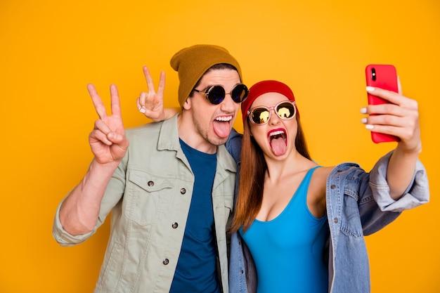 Raffreddare moderno due persone studenti usano smartphone fare selfie v-sign mostra lingua-fuori estate resto blogging indossare berretto camicia blu costumi da bagno denim jeans giacca isolato brillante brillante colore sfondo