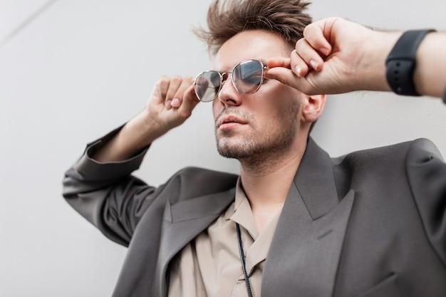 Bel ritratto di un bell'uomo d'affari con acconciatura e barba in abiti alla moda con giacca e camicia guardando attraverso gli occhiali da sole vicino a uno sfondo grigio per strada