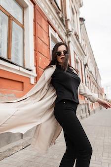 Cool piuttosto giovane donna hipster in occhiali da sole vintage in abbigliamento casual elegante nero in trench moda primavera gira all'aperto vicino al vecchio edificio sulla strada. modello di moda ragazza carina alla moda in città.