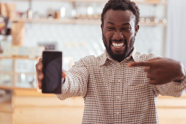 Ottimo acquisto. felice giovane uomo seduto nella caffetteria e indicando il suo nuovo telefono mentre ride felicemente