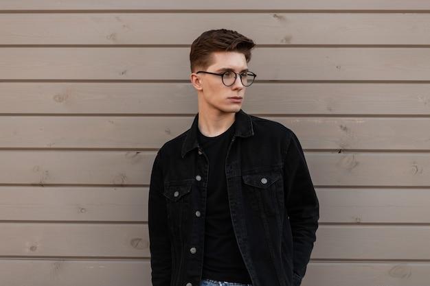 Un giovane serio e alla moda in abiti alla moda in denim con occhiali alla moda sta riposando vicino a un edificio in legno sulla strada