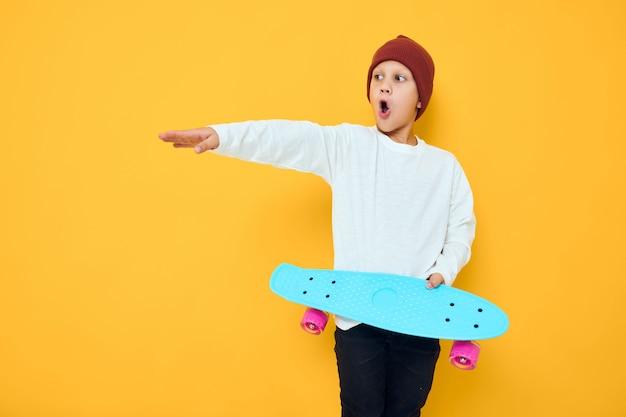 Cool ragazzo sorridente casual blu skateboard infanzia concetto di stile di vita
