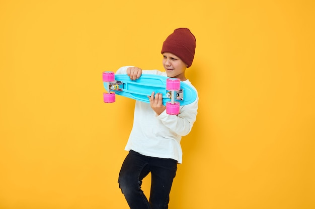 Cool ragazzo sorridente in uno skateboard con cappello rosso nelle sue mani sfondo isolato
