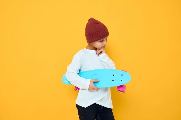 Fresco ragazzo sorridente con uno skateboard con cappello rosso nella posa dello studio delle mani