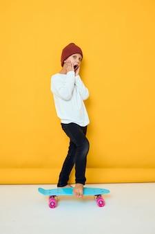 Ragazzo sorridente fresco in un concetto di stile di vita dell'infanzia di intrattenimento di skateboard maglione bianco